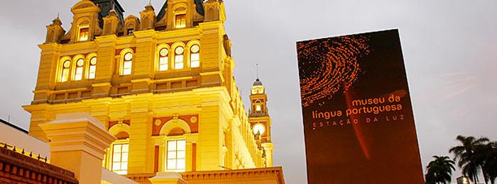 """Foto mostra a fachada do Museu da Língua Portuguesa, que fica no prédio da Estação da Luz. Do lado direito da imagem, há uma placa com os dizeres """"Museu da Língua Portuguesa - Estação da Luz"""""""