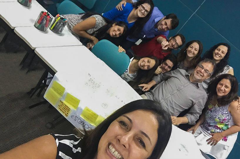 Selfie com 11 pessoas, entre homens e mulheres. Uma das mulheres está mais à frente do grupo e é quem tira a foto. O restante está atrás de uma mesa com cartazes e postits. Todos estão sorrindo e demonstrando animação.