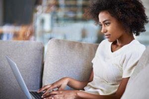 Foto de uma mulher negra, com cabelo afro e blusa branca, mexendo em um laptop. Foto se relaciona ao workshop de conteúdo acessível em marketing digital do instituto FeAfro