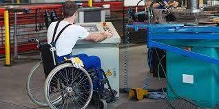 Foto em plano aberto que mostra um cadeirante com uniforme de atividades industriais operando uma máquina. Imagem ilustra mercado de trabalho para pessoas com deficiência