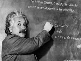Albert Einstein olha para câmera e indica uma fórmula escrita no quadro negro
