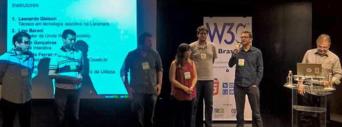 Foto de um palco com seis homens e uma mulher. Um dos homens fala ao microfone. Ao fundo, do lado esquerdo, está a projeção de uma apresentação; do lado direito, um banner do W3C Brasil.