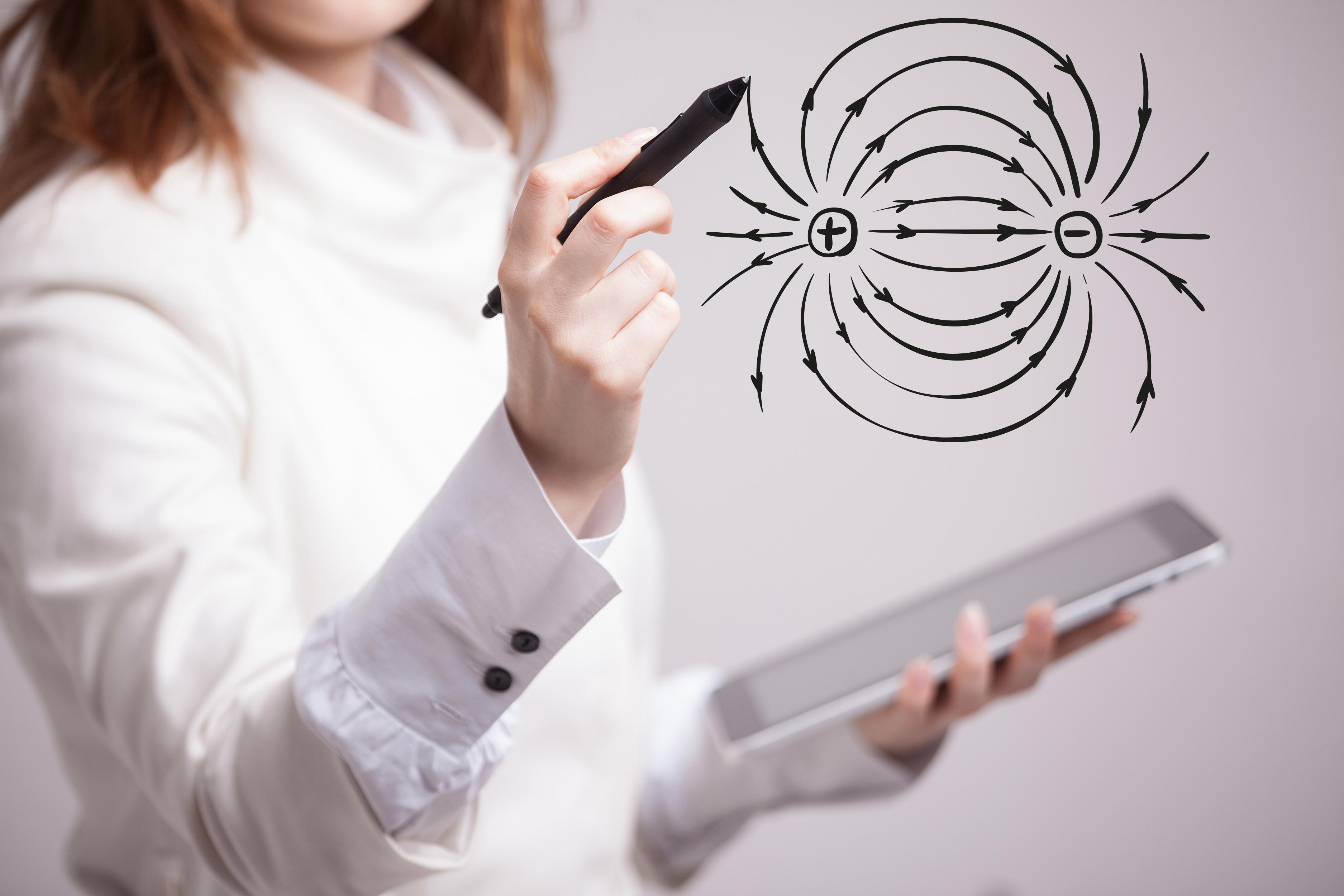 Foto de uma mulher em pé com um tablet e uma caneta nas mãos. Ela usa a caneta como se estivesse desenhando no ar