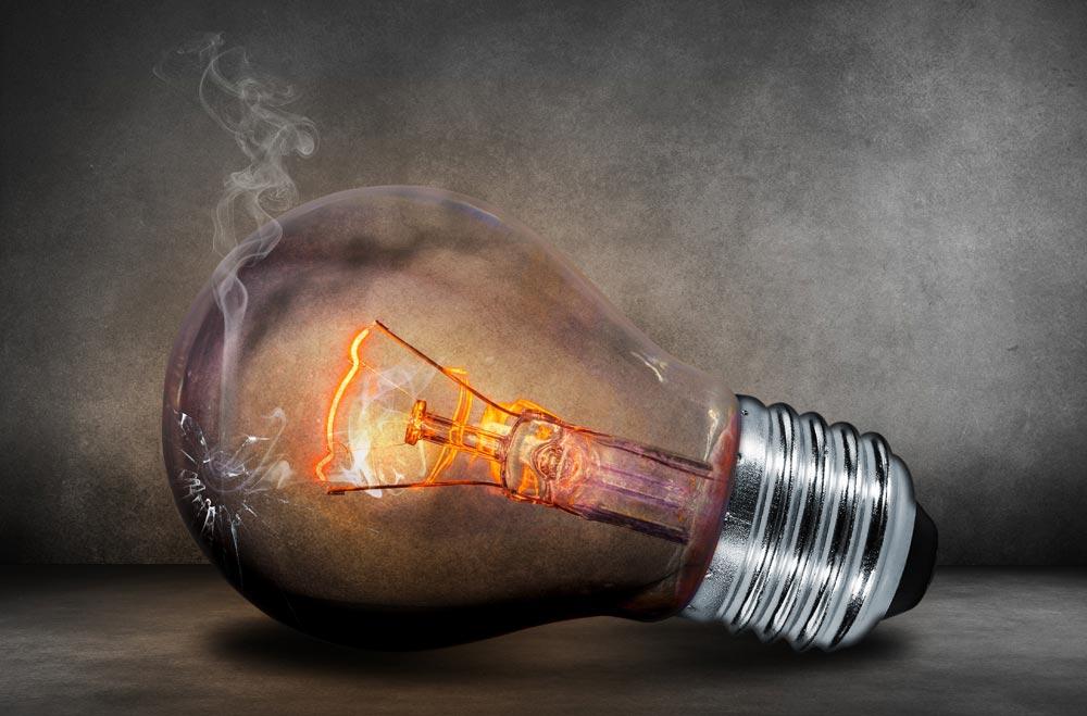 Arte realista com uma lâmpada na horizontal. Ela está com o vidro rachado e saindo fumaça