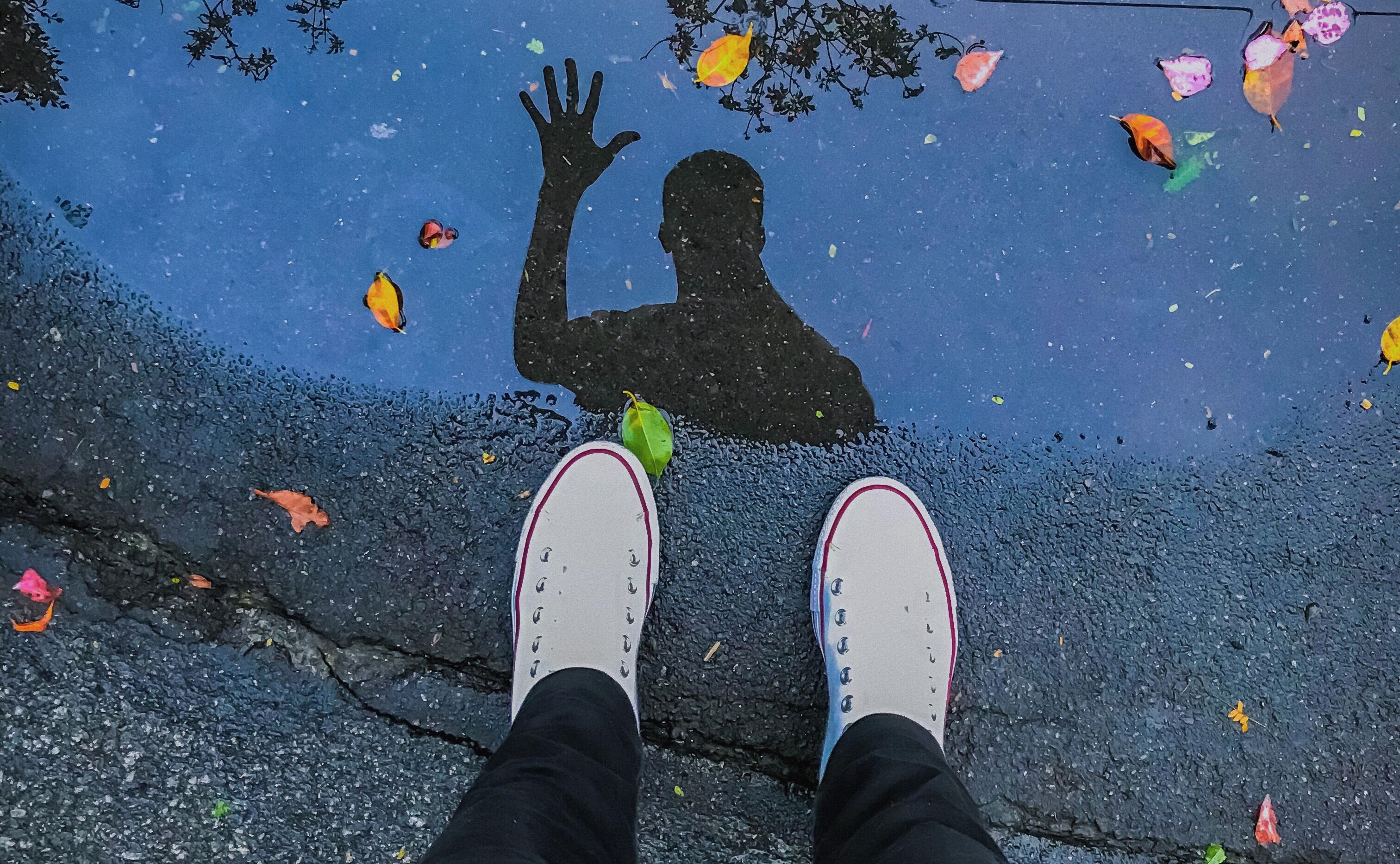 oto dos pés com all star branco e uma poça d'água no chão. No reflexo, há a silhueta de um homem acenando com a mão aberta. Na água da poça, também há folhas e pétalas de flores.