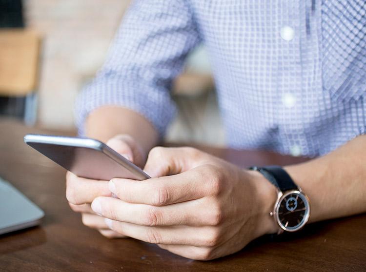 Foto de mãos segurando um celular