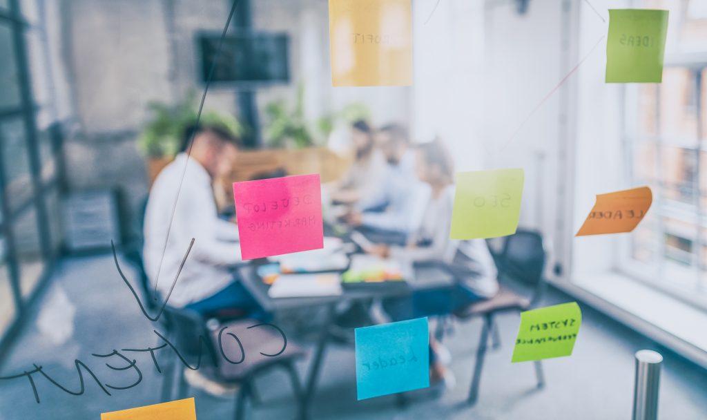 Foto de um escritório com jovens em uma reunião, com parede de vidro com post its coloridos